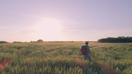 Woman with Backpack walking through farm fields