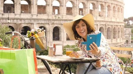 Happy young woman tourist taking selfies with smartphone at the table outside a bar restaurant in front of the Colosseum in Rome with coffee, juice and cornetto. Elegant beautiful dress with large hat and colorful shopping bags.