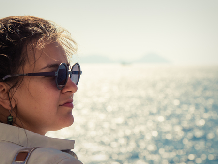 Young woman with sunglasses enjoying the breeze on a ship travel at sea.