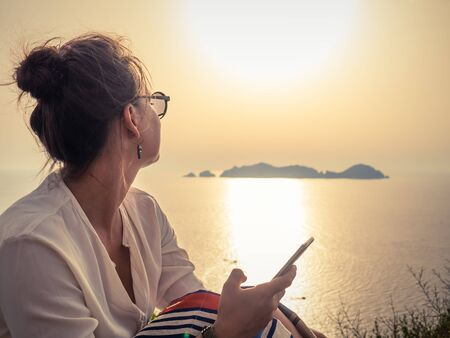 Young woman using smartphone at sunset in front of the sea on Ponza island coast