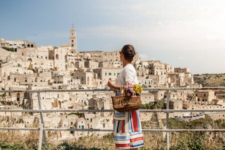 Young elegant woman tourist in historical Matera town in Italy walking looking at city landscape from railing