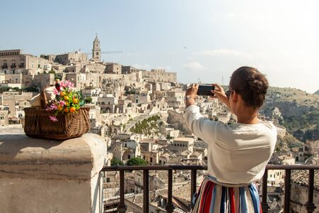 Young elegant woman tourist in historical Matera town in Italy taking photos with smartphone
