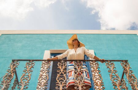 Beautiful young girl on balcony of a blue house in a colorful fashion dress with large hat in Sunny weather, in Ponza island Italy Stock Photo