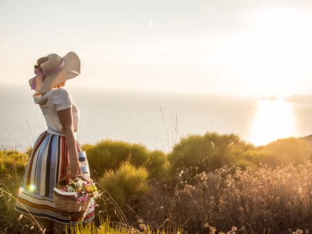 Young woman with flowers basket enjoying sunset view on the hill over the seaside. Large hat, fashion white shirt, colorful skirt. 写真素材