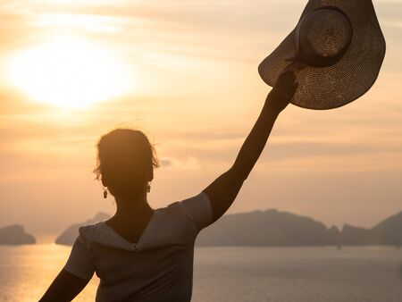 Young woman waving large hat in front of sunset view on the hill over the seaside. Fashion white shirt, colorful skirt, flowers basket.
