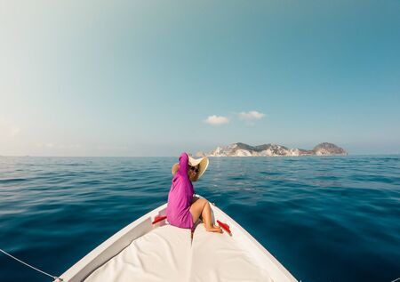 Young woman sitting on bow of boat in the middle of the sea. Happy girl with hat raising hands enjoying freedom travel.