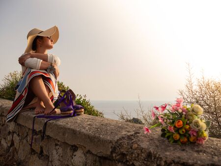 Young woman sitting on a wall at sunset in front of the sea on Ponza island coast. Fashion white shirt, colorful skirt, large hat, flowers bouquet.