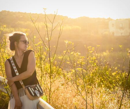 Young woman in green nature at sunset on Ponza Island Italy. Fashion black dress, purse and sunglasses. Summer evening. 写真素材