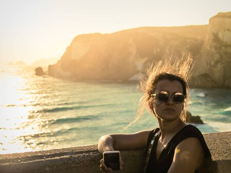 Young woman sitting at sunset in front of the sea on Ponza island coast. Hair in the wind, fashion sunglasses. 写真素材