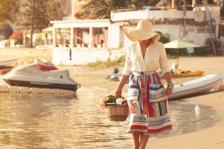 Young woman walking barefoot on the beach in Ponza Island harbor, Italy. Fashion white shirt and colorful skirt, basket with flowers, book and wine bottle.
