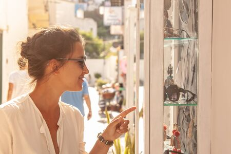 Young woman looking at small shop window in a colorful street on Ponza island town, Italy. Fashion dress and sunglasses. Stockfoto