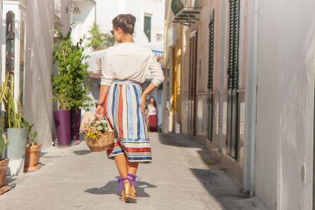 Young woman walking in a typical alley on Ponza island town, Italy. Fashion dress and sunglasses, white building.