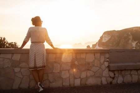 Young woman standing looking at sunset in front of the sea on Ponza island coast, on a wall with view of the ocean. 9768