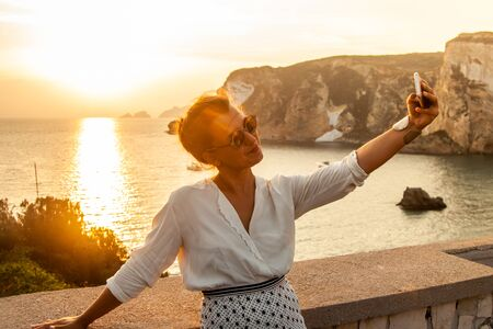 Young woman with smartphone taking selfies with sunset in front of the sea on Ponza island coast, on a wall with view of the ocean. 9826