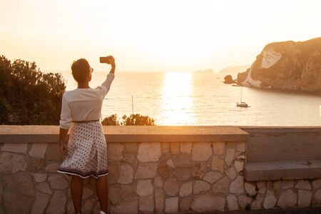 Young woman with smartphone taking pictures of sunset in front of the sea on Ponza island coast, on a wall with view of the ocean. 9772 Zdjęcie Seryjne