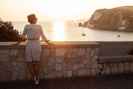 Young woman standing looking at sunset in front of the sea on Ponza island coast, on a wall with view of the ocean. 9771