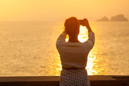 Young woman with smartphone taking pictures of sunset in front of the sea on Ponza island coast, on a wall with view of the ocean. 9851