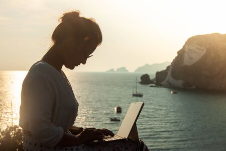 Young woman using laptop computer at sunset in front of the sea on Ponza island coast, sitting on a wall with view of the ocean. 9725