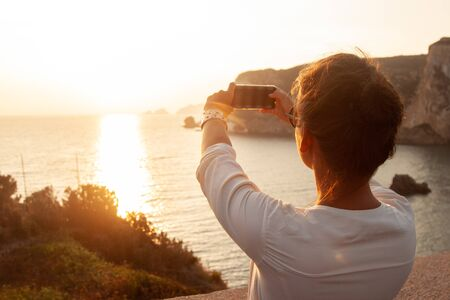 Young woman with smartphone taking pictures of sunset in front of the sea on Ponza island coast, on a wall with view of the ocean. 9779 Zdjęcie Seryjne