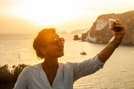 Young woman with smartphone taking selfies with sunset in front of the sea on Ponza island coast, on a wall with view of the ocean. 9831