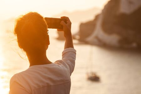 Young woman with smartphone taking pictures of sunset in front of the sea on Ponza island coast, on a wall with view of the ocean. 9777 Zdjęcie Seryjne