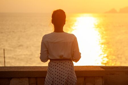 Young woman standing looking at sunset in front of the sea on Ponza island coast, on a wall with view of the ocean.