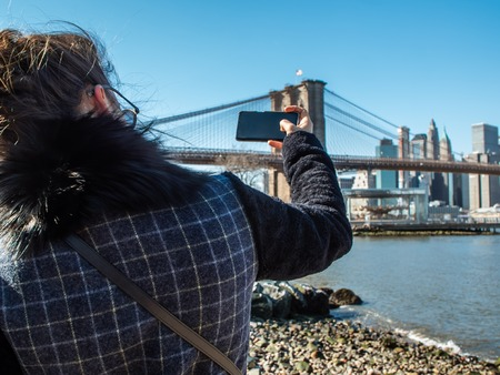 Young Woman tourist by the river in Dumbo taking pictures of Brooklyn Bridge and Cityscape of New York skyline.