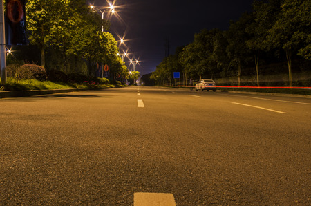 clues: Asphalt road and the skyline of a city on the lighting Stock Photo