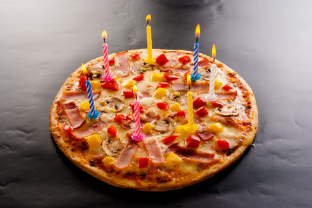 Festive candles pizza with ham, mushrooms, cheese and sweet pepper top view Stock Photo