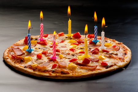 Festive candles pizza with ham, mushrooms, cheese and sweet pepper top view Banco de Imagens