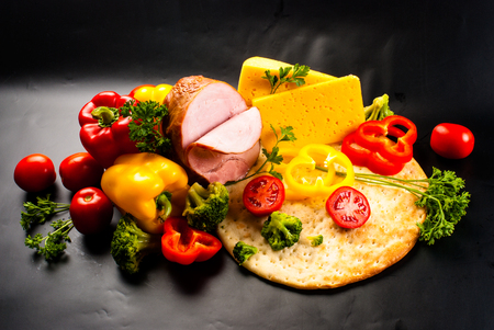 foodstuff: still life - set of pizza on black background - vegetables, herbs, ham, cheese, seasonings Stock Photo