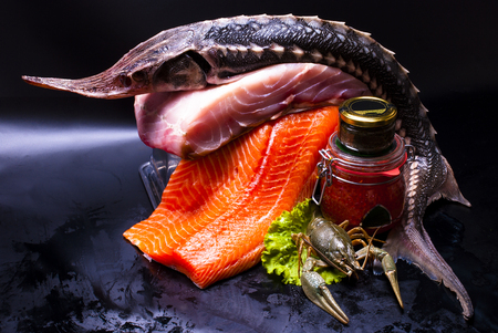 still life - salmon, caviar, cancer on the black background