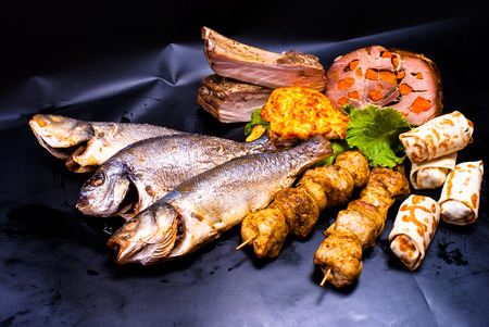 pescado frito: still life - meat with stuffed, shish kebab, steak in batter, crepes with fillings, fried fish on the black background Foto de archivo
