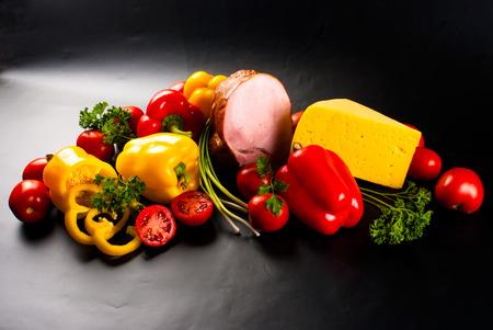 Stillleben - Reihe von Pizza auf schwarzem Hintergrund - Gemüse, Kräutern, Schinken, Käse, Gewürze