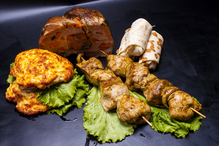 fillings: still life - meat with stuffed, shish kebab, steak in batter, crepes with fillings on the black background Stock Photo