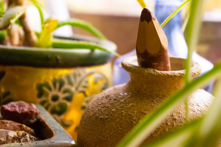 pot light: Still life with brown pencil in old clay jar Stock Photo