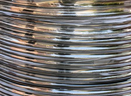 bobina: una bobina de cable eléctrico de plata, fondo