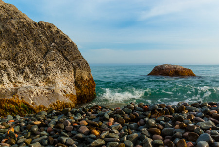 dungy: The sun sets illuminating the wet rocks and pebble beaches of the Crimean Coast