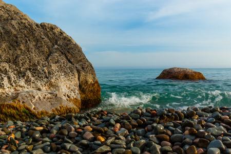 The sun sets illuminating the wet rocks and pebble beaches of the Crimean Coast
