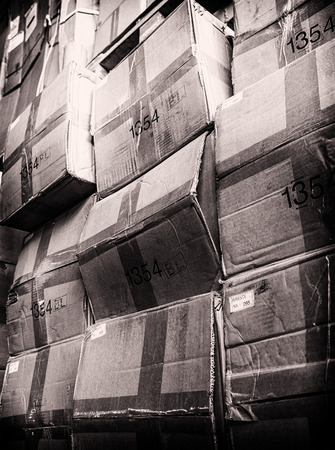 rack arrangement: rack stack arrangement of vintage cardboard boxes in a store warehouse, toned photo Stock Photo