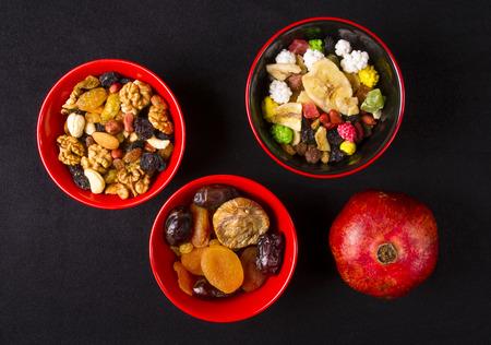 frutas deshidratadas: varias tuercas de la mezcla, frutos secos y frutas frescas en el fondo negro
