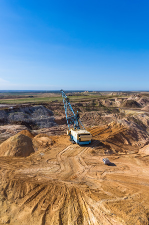 dragline: the big dipper dragline excavator digging clay on blue sky background Stock Photo