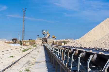 dumper: conveyor and dumper - warehouse production in quarry blue clay on sky background