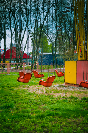 chain swing ride: empty spring old amusement Park, chain swing carousel awaits visitors, FILTERED for retro effect