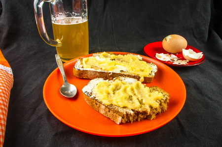 unfiltered: the bachelor dinner - toast with butter and yellow caviar, boiled eggs and unfiltered beer Stock Photo