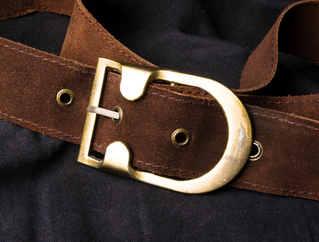 buckle: closeup of the brown suede strap with yellow metal buckle