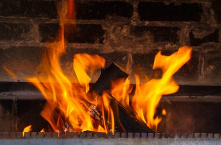 warmth: heating, warmth, fire and cosiness concept - close up of burning fireplace at home
