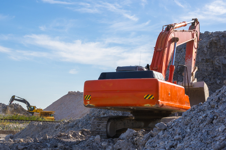dredging: excavator and dumper - warehouse production in quarry blue clay on sky background Stock Photo
