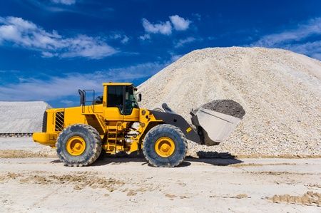 dredging: forklift - warehouse production in quarry blue clay on sky background Stock Photo