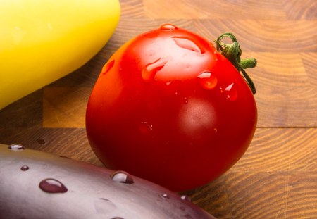 still life - yellow pepper, tomato and eggplant on wooden Board Stock Photo
